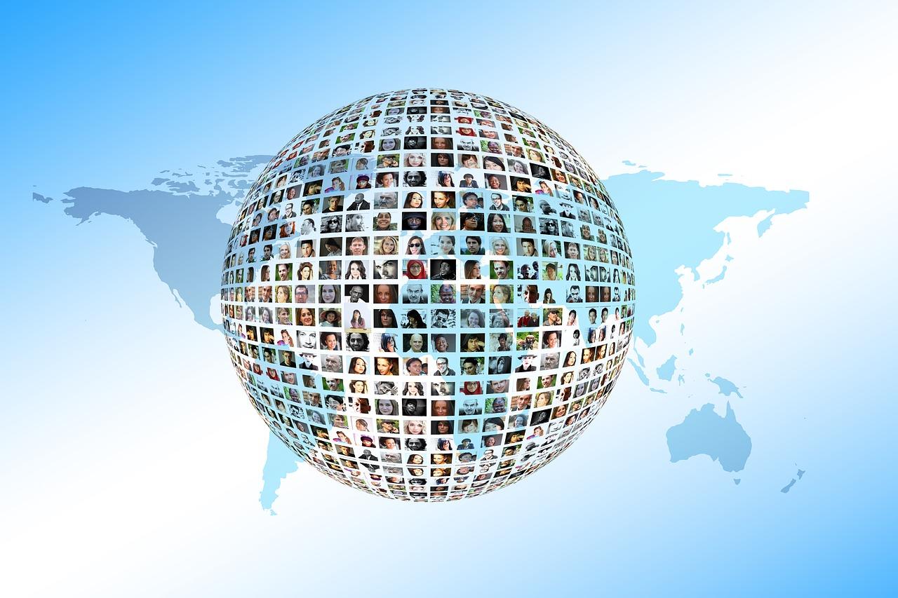 Sinertävän taustan päällä harmaa maailmankartta levitettynä. Kartan päällä leijuu maapallon muotoinen pallo, jonka pintaa peittävät pienet ihmisten kasvokuvat.