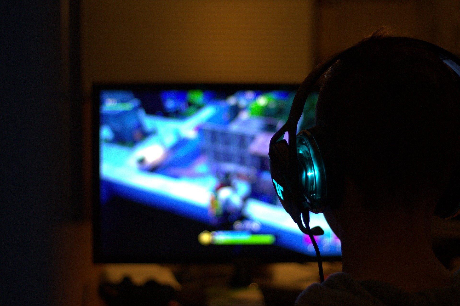 Henkilö, jolla on pelikuulokkeet päässä kuvattuna takaapäin. Henkilön edessä on tietokoneen näyttö, jossa näkyy sumeasti henkilön pelaama tietokonepeli. Kuvaa blogia aiheesta nuorisotyö pelikulttuurissa.