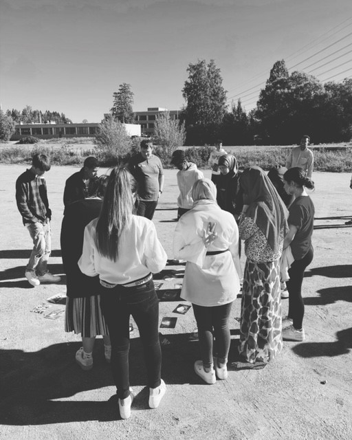 Ryhmä nuoria seisoo ringissä hiekkakentällä