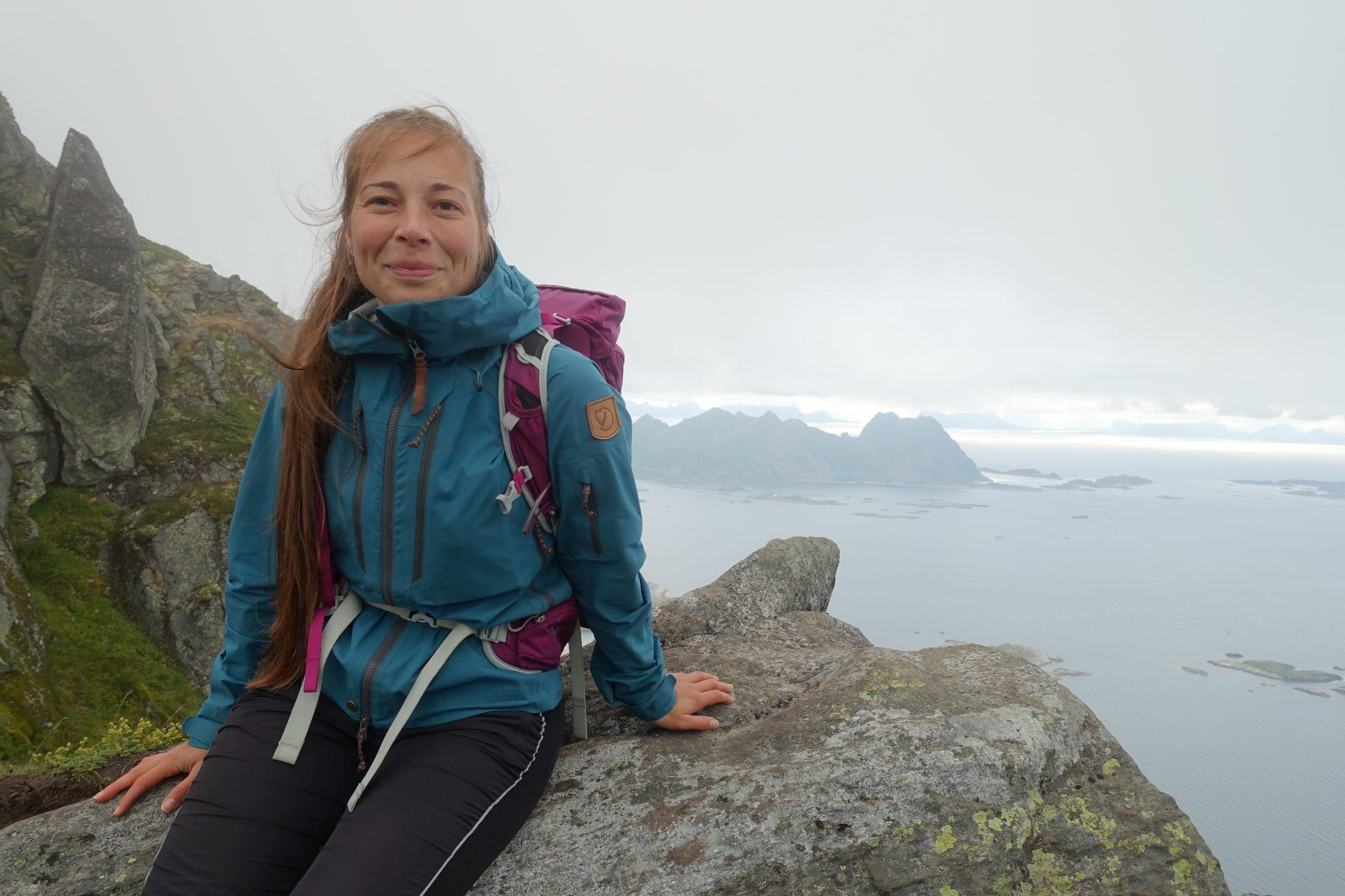 Nuori nainen hymyilee istuessaan korkean vuoren reunalla Norjan vuoristossa Lofotenilla.