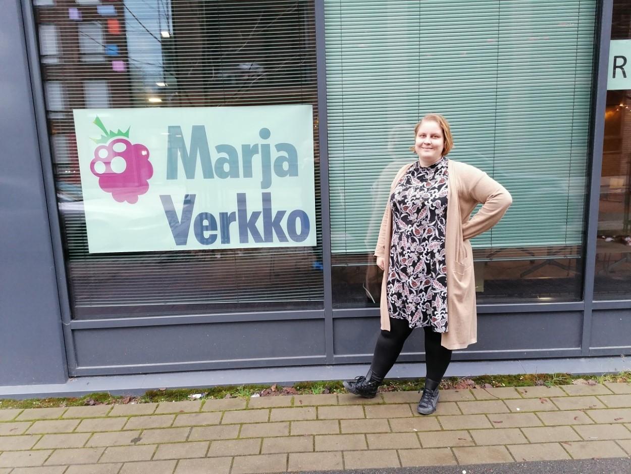 Nainen seisoo työpaikkansa ulkopuolella yllään beige neuletakki sekä kuviollinen mekko.