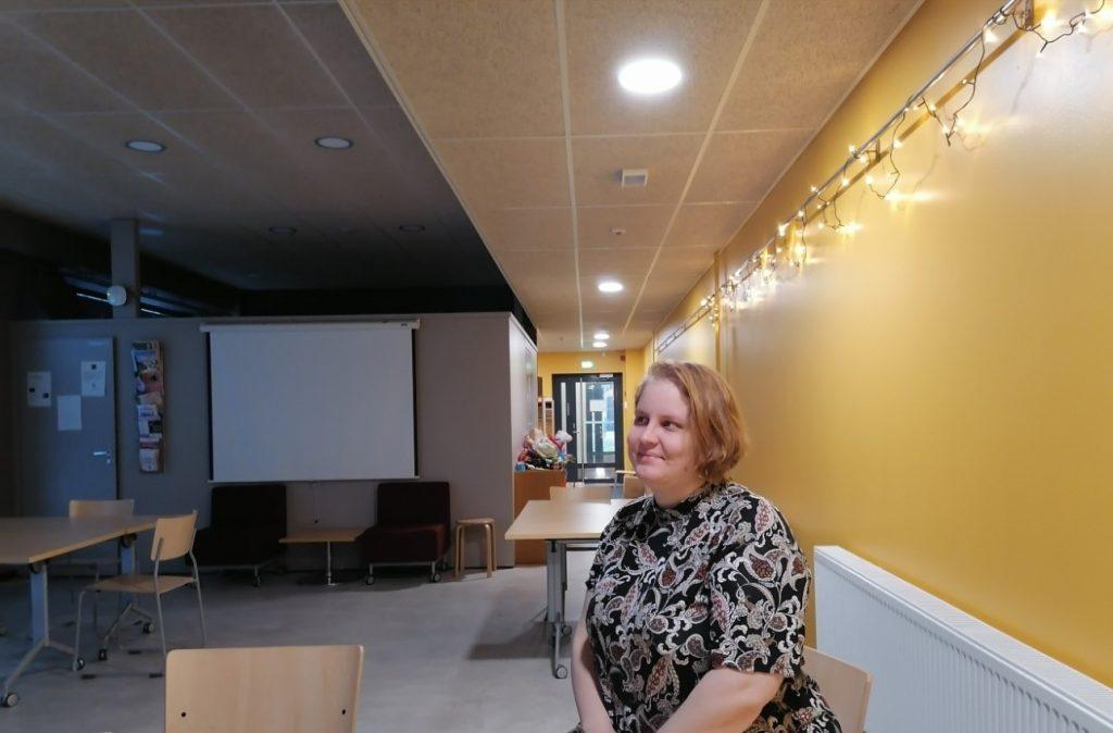 Nainen istuu pöydän ääressä työpaikallaan yllään kuviollinen lyhythihainen mekko ja takanaan tunnelmalliset jouluvalot.