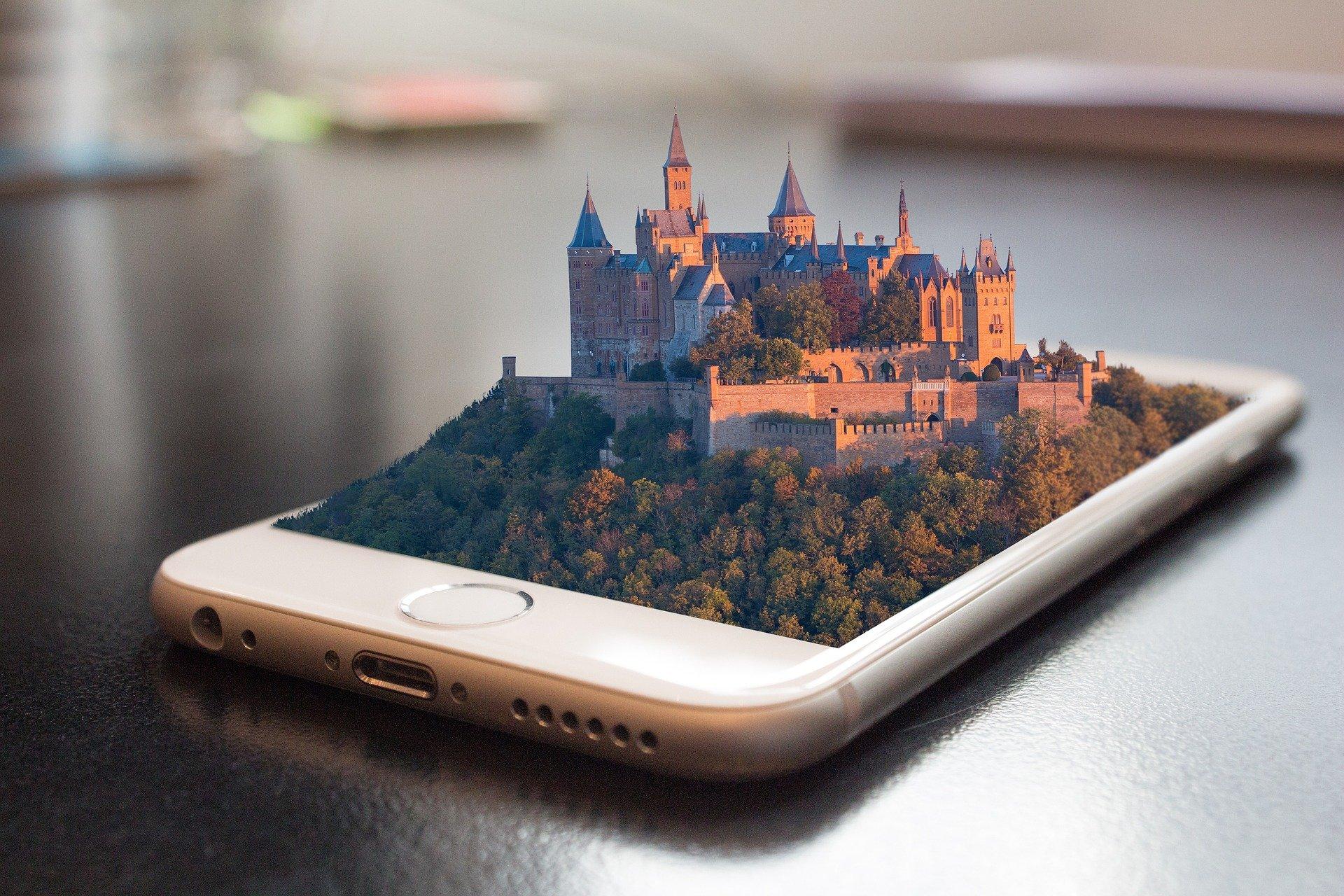 Valkoisesta älypuhelimesta kohoaa kolmiulotteisesti kukkula, jonka laella seisoo linna. Linnaa ympäröi jykevä muuri sekä vihreä metsä.