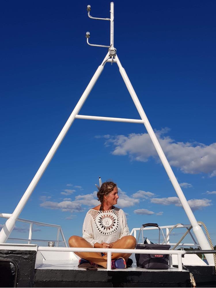 Nainen istuu valkoisessa neulepaidassa jalat ristissä laivan kannella, metallisen kolmirakenteen alla, taustalla sininen taivas, jossa vähän valkoisia pilviä. Nainen katsoo hymyillen vasemmalleen. Kuvassa paljon taivasta.