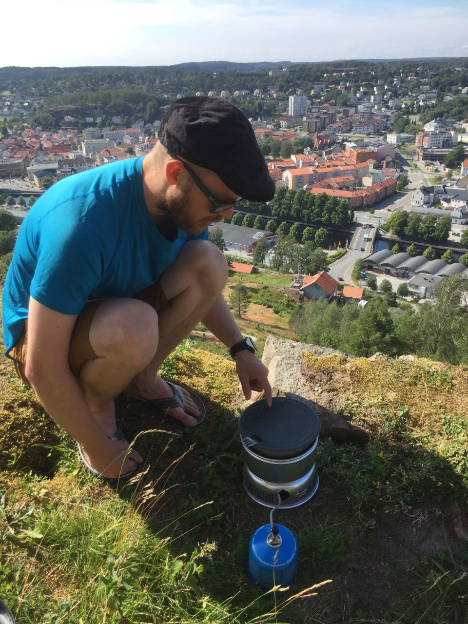 A man using a portable cooker on top of a hill in Norway overlooking a city.