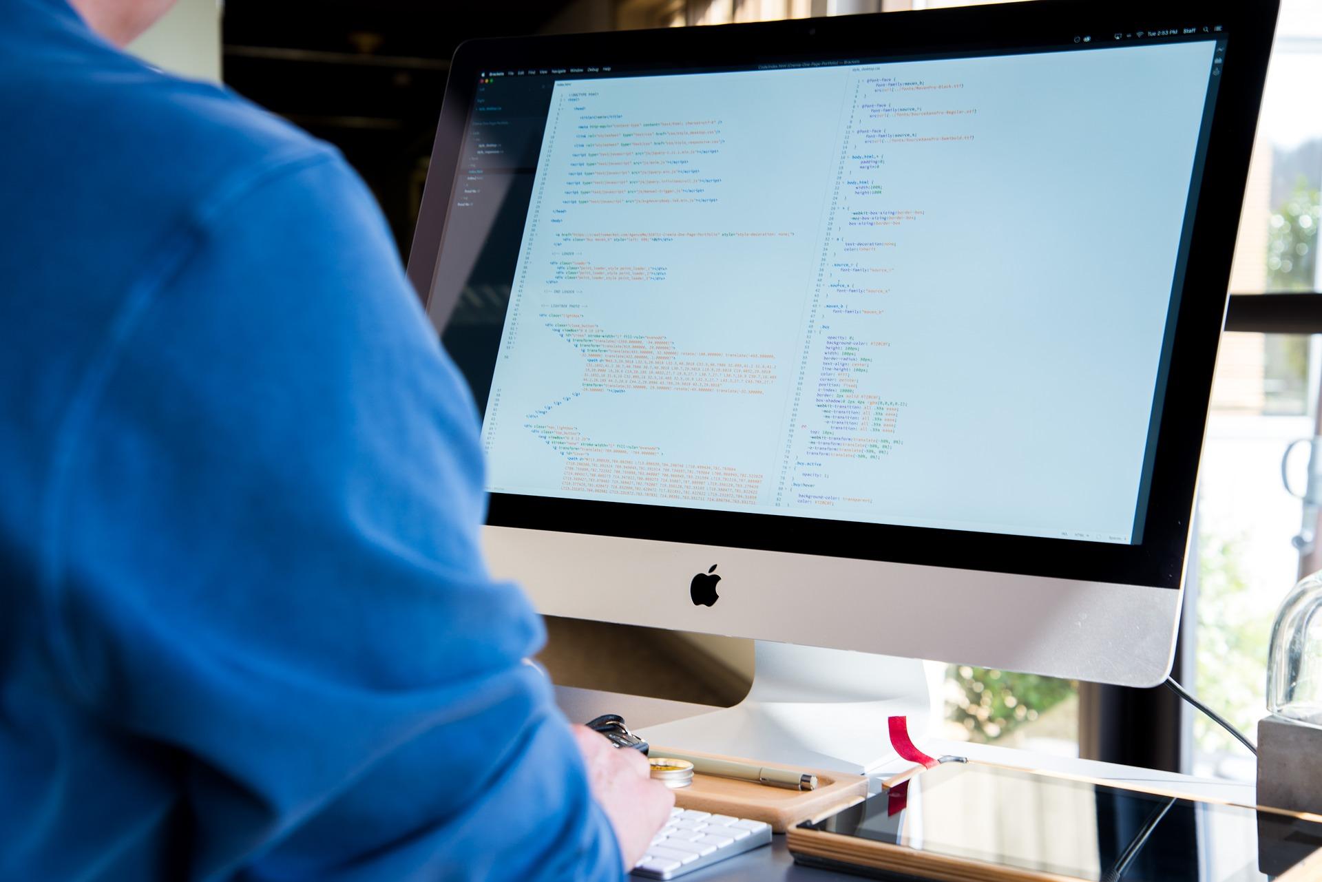 Tietokoneen kuvaruutu, jolla teknistä tekstiä ja mieshahmo osaselkäkuvassa, sininen paita.