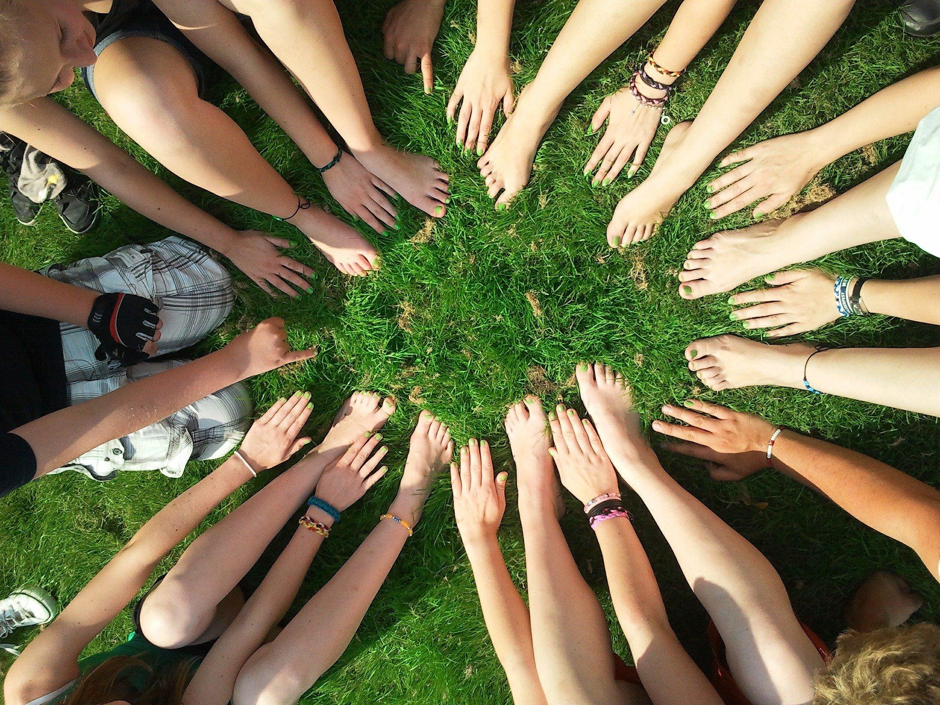 Vihreällä nurmikolla joukko ihmisiä ympyrämuodoksessa, jossa heistä näkyy vain paljaat jalat ja kädet.