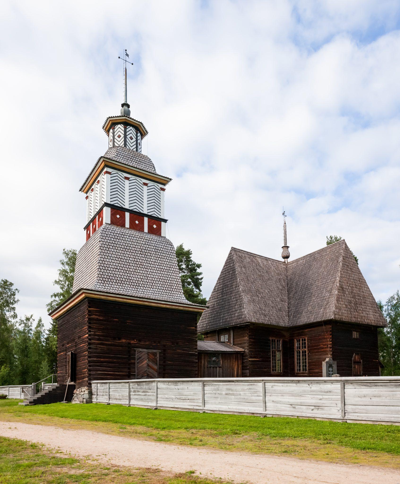 Petäjäveden vanha kirkko. Tumma ja korkea vanha puukirkko seisoo vasten sinistä taivasta.