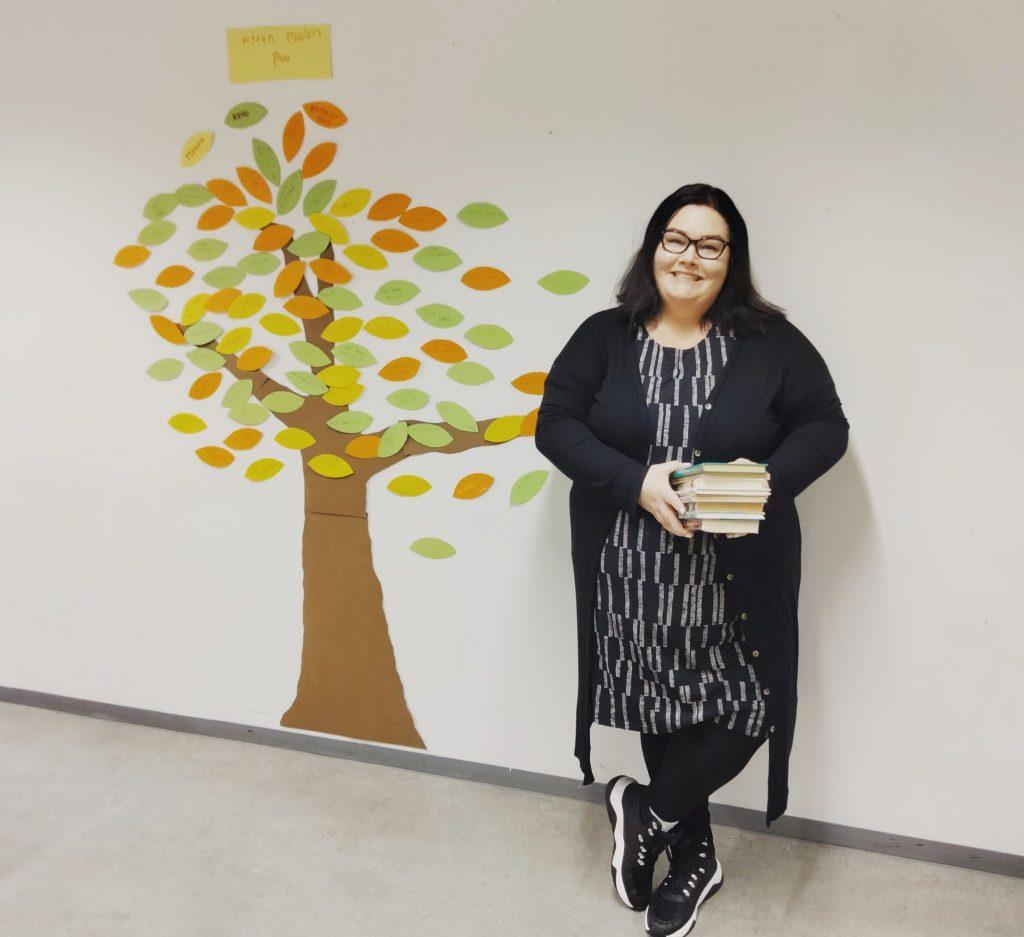 Katri Hytönen nojaa valkeaan seinään. Seinään on laitettu värikäs puu tarroina. Hymyilevällä ja silmälasipäisellä naisella on musta harmaa hame ja villatakki, kädessään kirjapino,