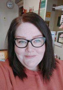Mustasankainen silmälasipäinen nainen, tummat yli olkapään laskeutuvat hiukset hymyillee punertavassa paidassa lähikuvassa, niukasti koulumainen tausta takanaan.