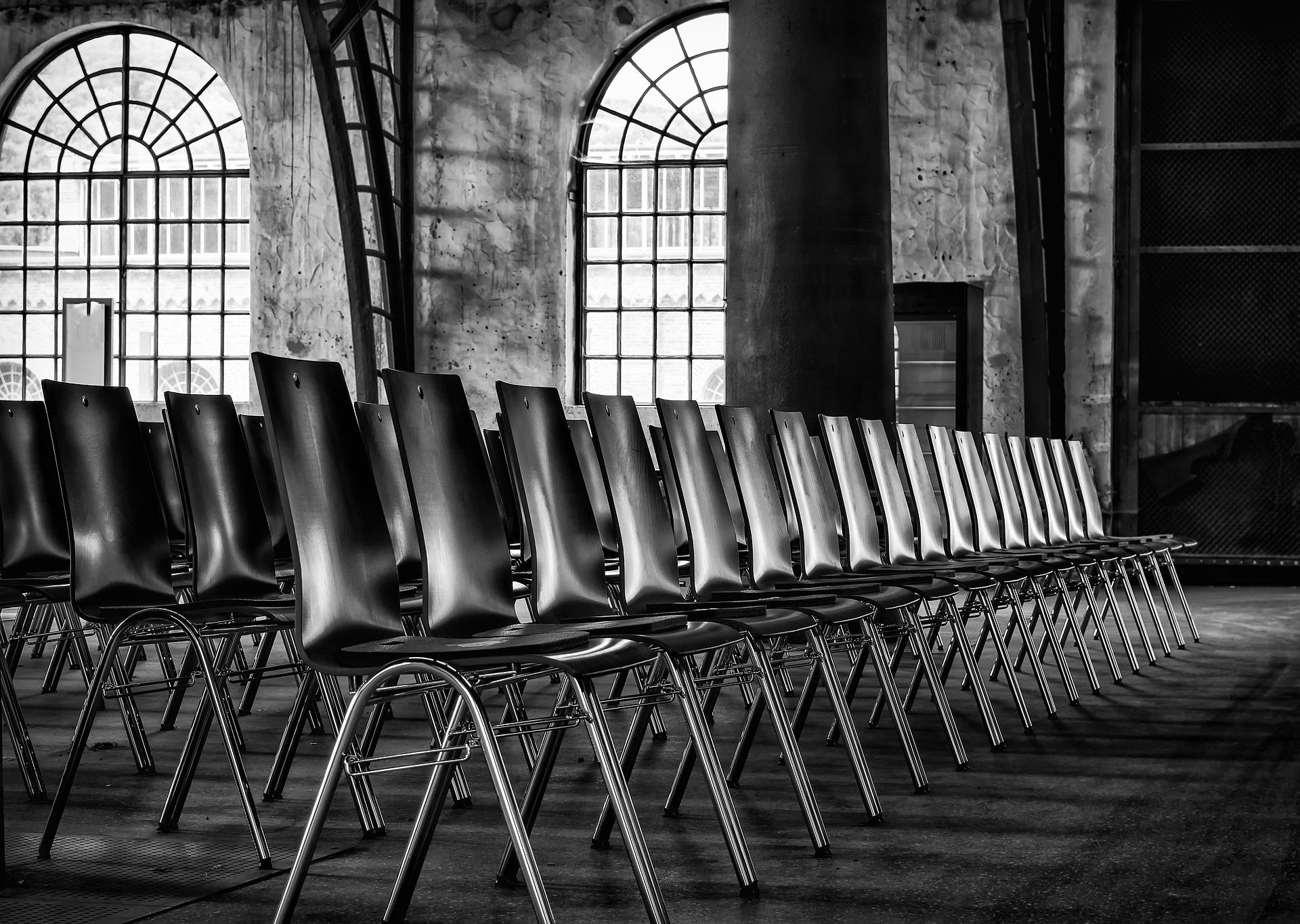 Mustavalkoinen kuva tapahtumatilasta, jossa on riveissä tyhjiä metallijalkaisia tuoleja. Taustalla on kaksi kaarimallista, pikkuisista ruuduista muodostuvaa ikkunaa ja kiviseinät.