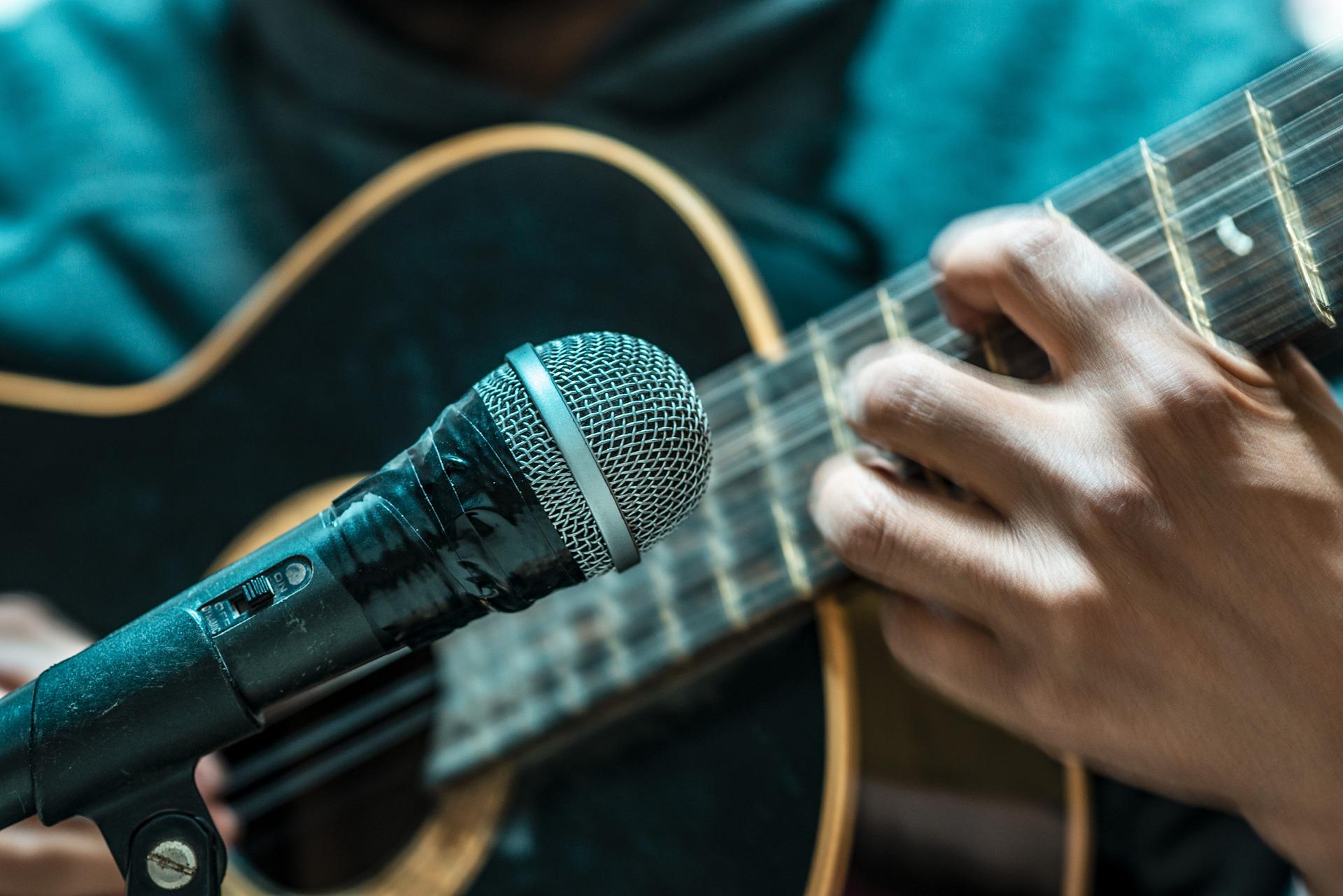 Henkilö soittaa akustista kitaraa lähellä mikrofonia. Lähikuva mikistä, sormista ja pienestä osasta kitaraa.