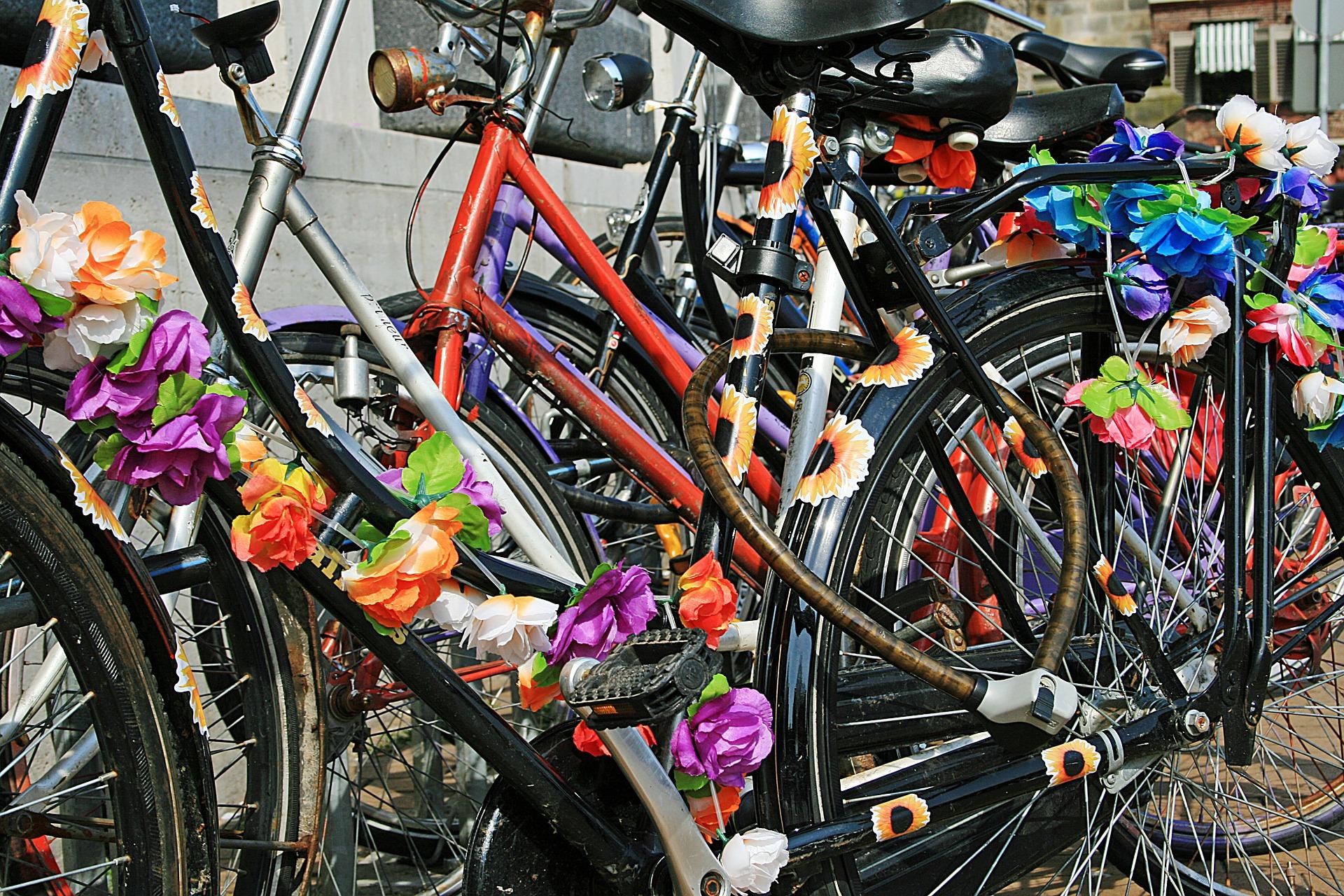 Telineessä oleviin polkupyöriin on sidottu paperista tehtyjä värikkäitä kukkia.