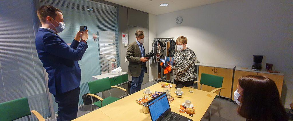Mies valokuvaa, kun toinen ojentaa kaulahuivia lahjaksi vieraana olevalle naiselle kokoushuoneessa.