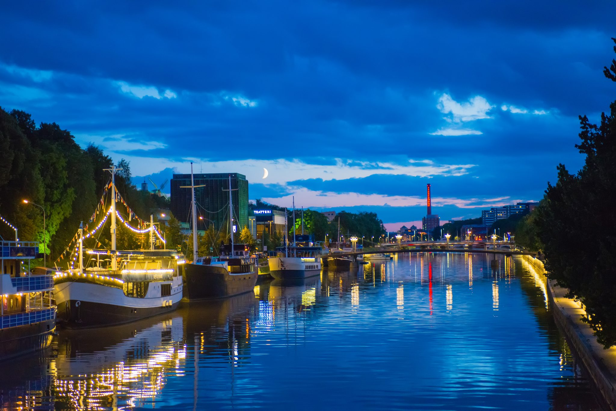 Ships are moored on the River Aura in Turku on a darkening summer night.