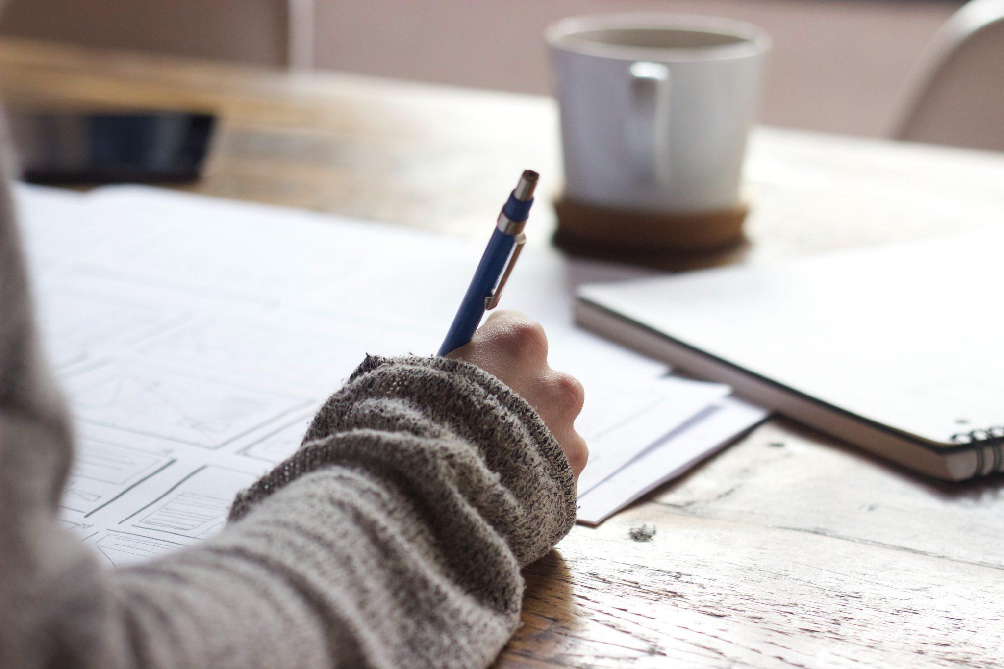 Henkilö pitelee kynää kädessään ja kirjoittaa paperille pöydä ääressä. Pöydällä on kahvikuppi.