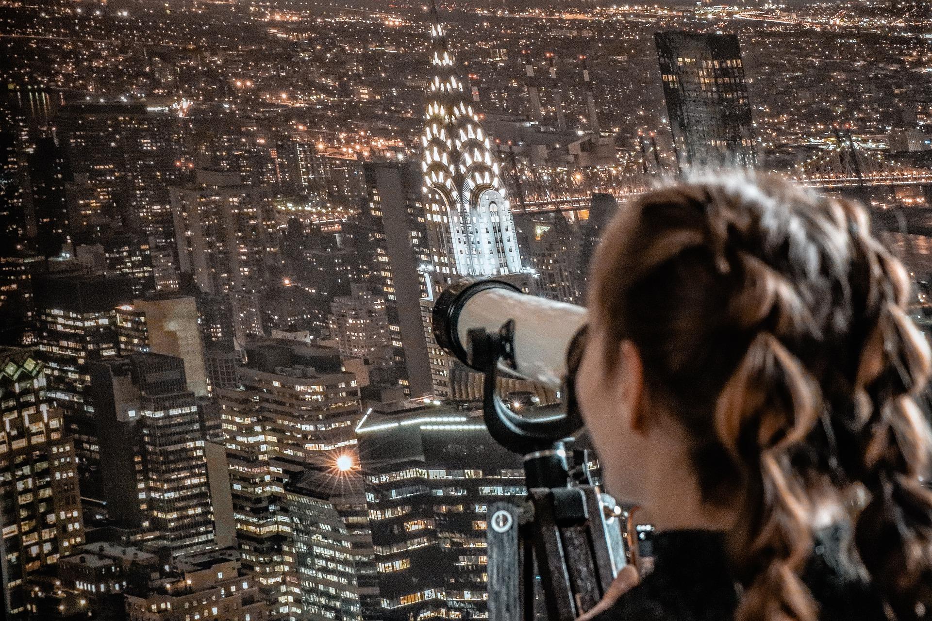 Hiukset palmikoituna oleva tyttö katselee kaukoputken läpi kohti New Yorkin maisemaa kattojen yläpuolelta.