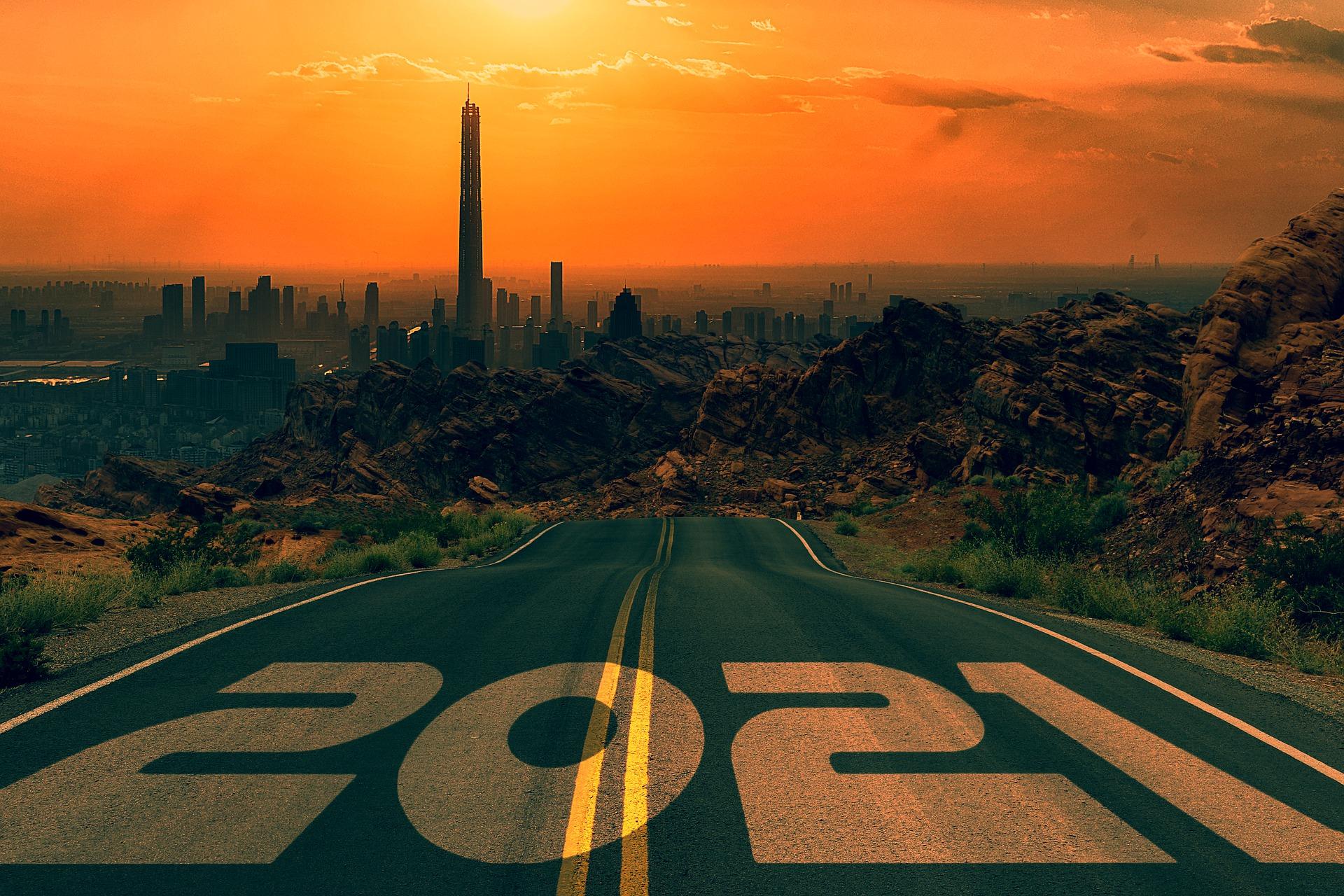 Oranssisävyinen maisemakuva, jossa 2021 luku etualalla, tie, joka johtaa kohti kaupungin siluettinäkymää.