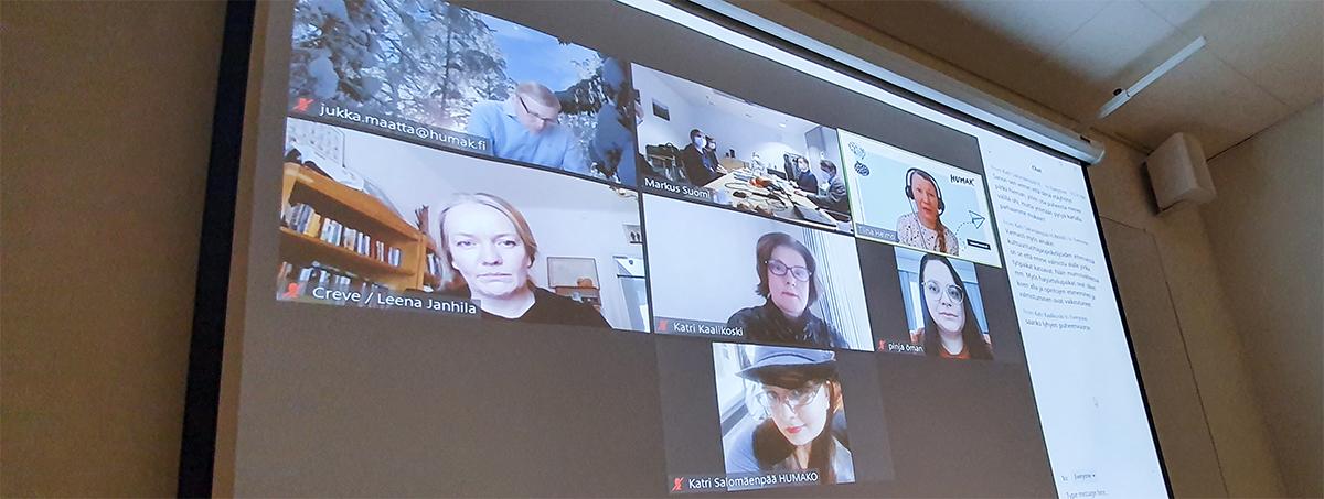 Verkkokokouspalvelun ikkuna osallistujista valkokankaalla. Kuvassa henkilöitä eri paikoissa.