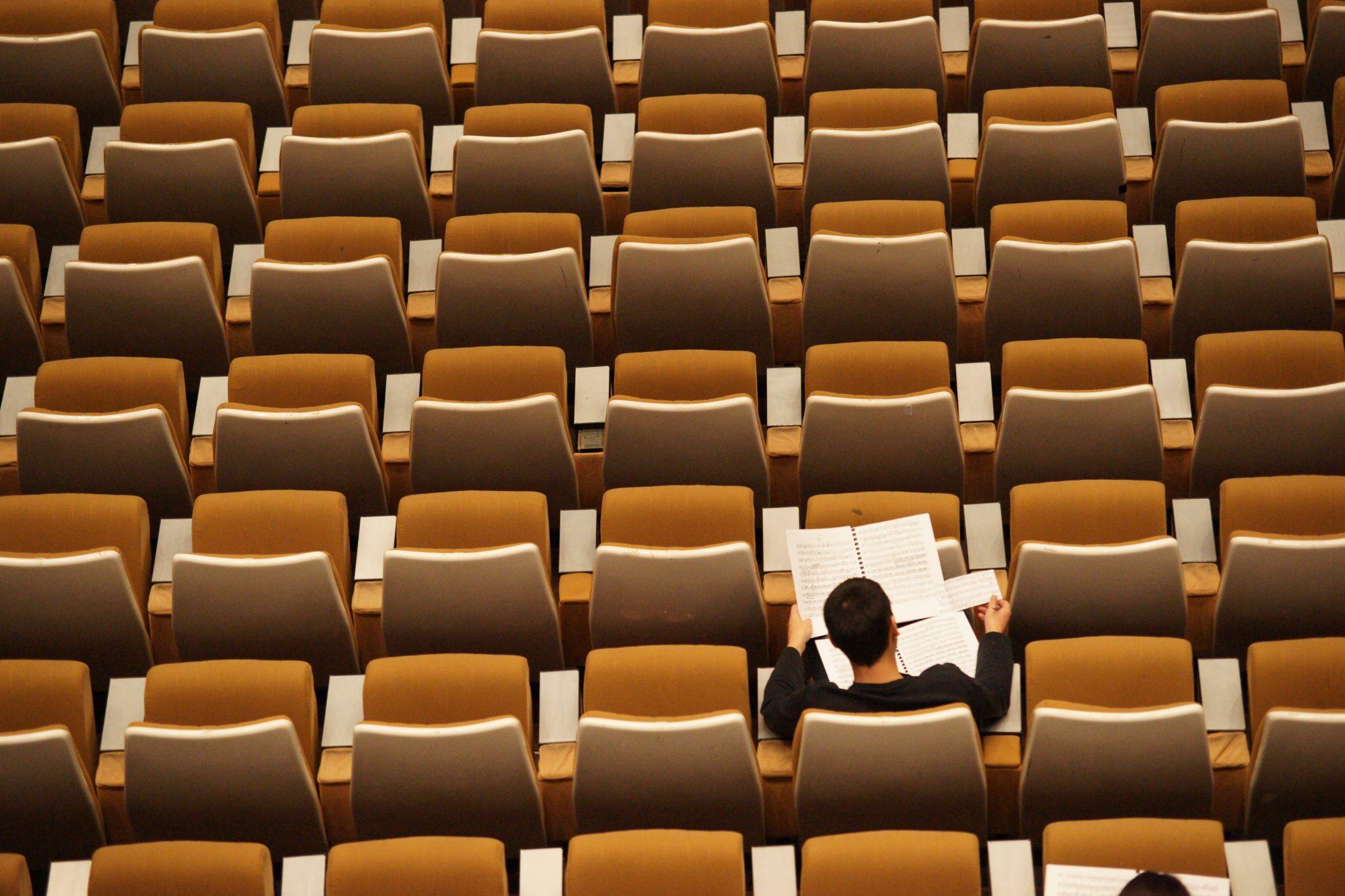 Tyhjiä penkkirivejä, yksi opiskelija istuu penkillä lukemassa nuotteja.