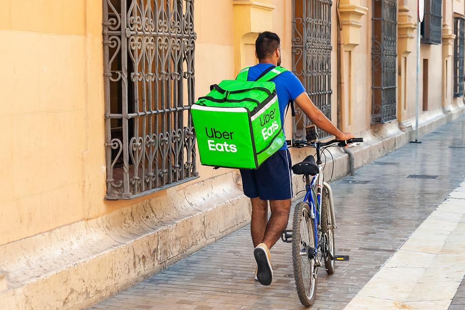 Kuvan keskellä on takaapäin kuvattu mies, joka työntää polkupyörää jalkakäytävällä. Miehellä on selässään suuri reppu, jossa lukee Uber Eats.
