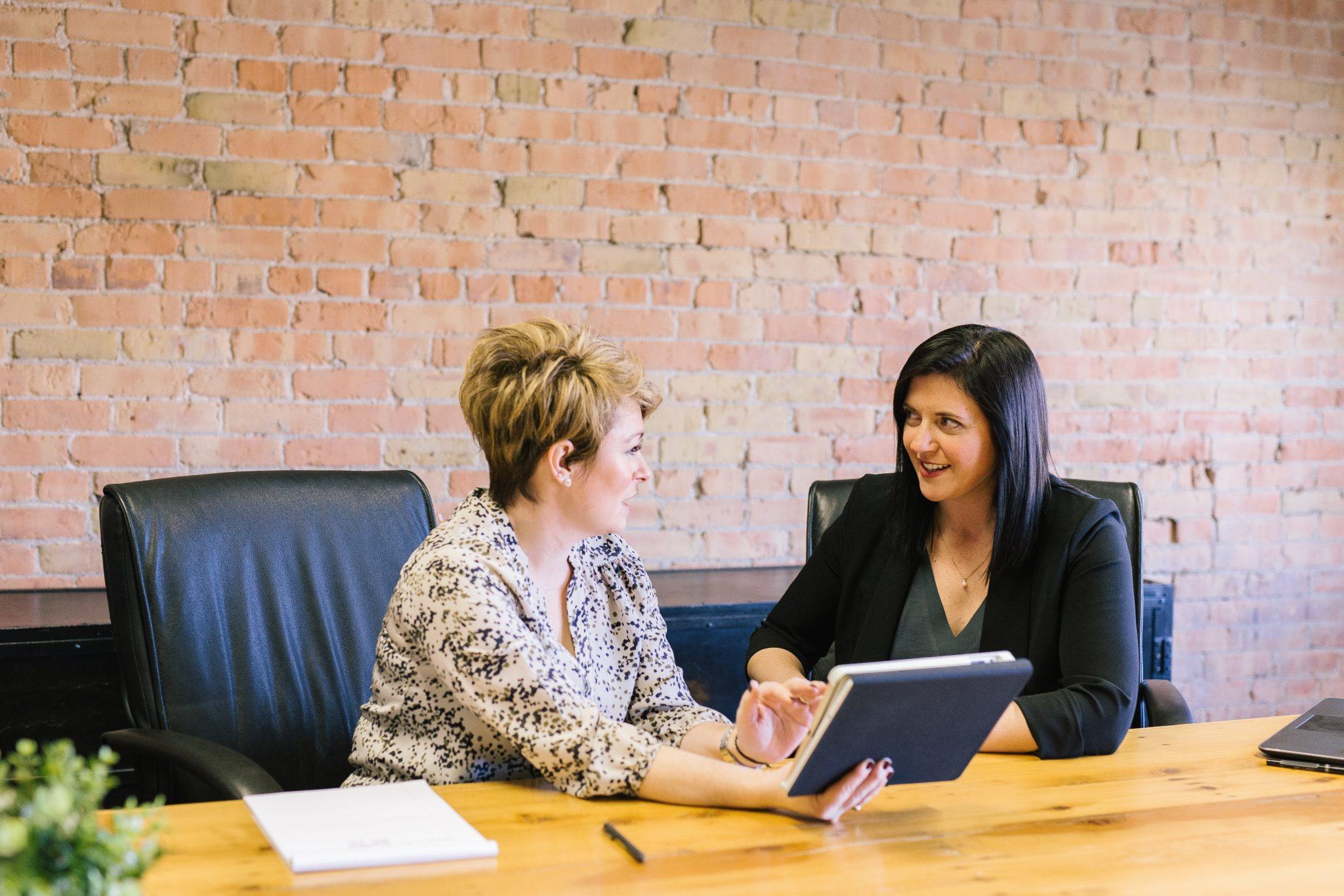 Kaksi naista keskustelee pöydän ääressä. Vasemmalla oleva nainen katsoo oikealla olevaa naista ja pitää kädessään kirjaa, joka on ehkä muistikirja.