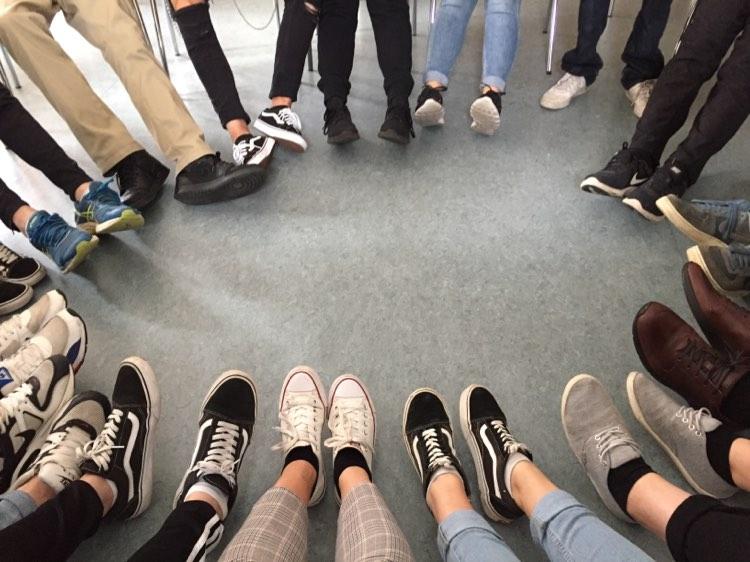 Nuoret istuvat tuoleilla ja muodostavat jaloillaan ringin.