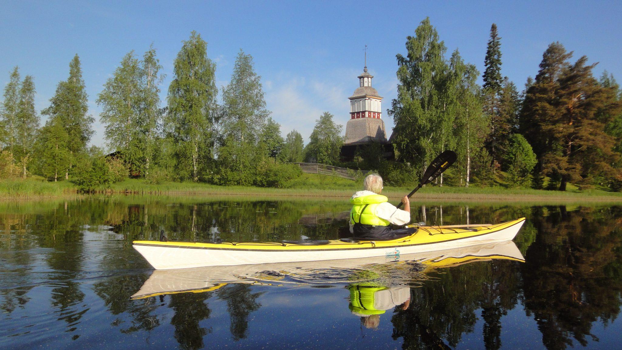 Henkilö meloo kellertävällä kanootilla ilta-auringossa kajakilla Unescon maailmanperintökohde Petäjäveden vanhan kirkon ohi ja päällään on keltainen pelastusliivi..
