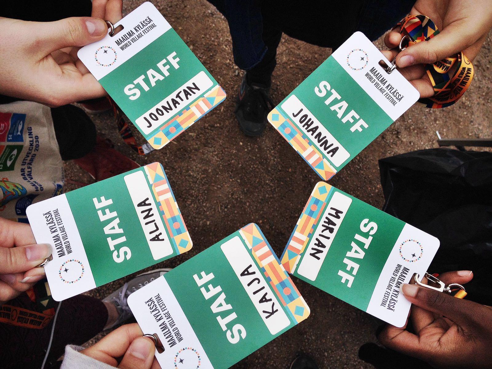 Viisi vihreä valkoista Maailmakylässä staffkorttia, noita ihmiset pitävät sormillaan kiinni muodostaen ympyrän, korteissa etunimi.
