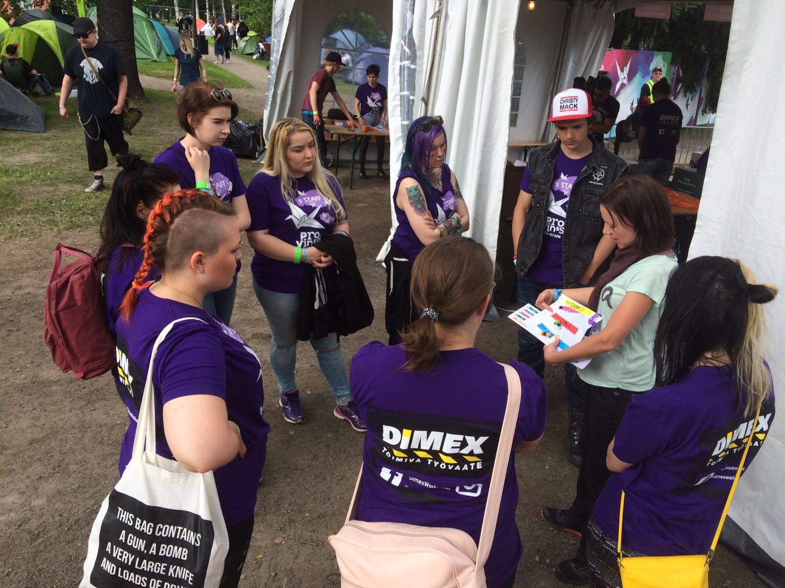 Seitsemän henkeä seisoo piirissä yhden pitäessä heille käskynjakoa, vapaaehtoistyöntekijöillä lilat paidat.