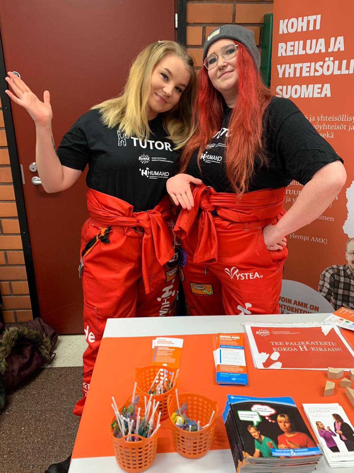 Kaksi hymyilevää opiskelijatyttyöä seisovat messupöydän takana päällään punaiset opiskelijahaalarit.
