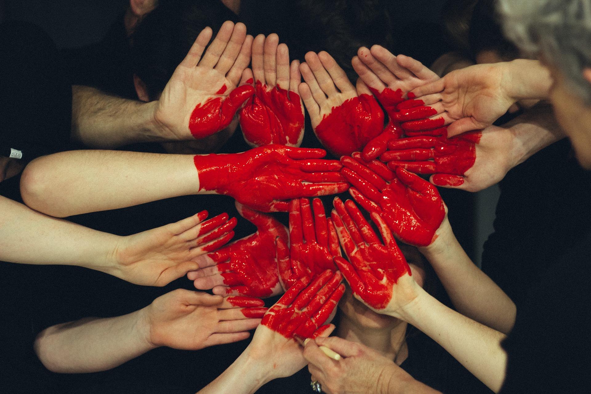 Ihmisten käsiä ryhmänä, käsissä on punaista maalia, joista muodostuu sydän.