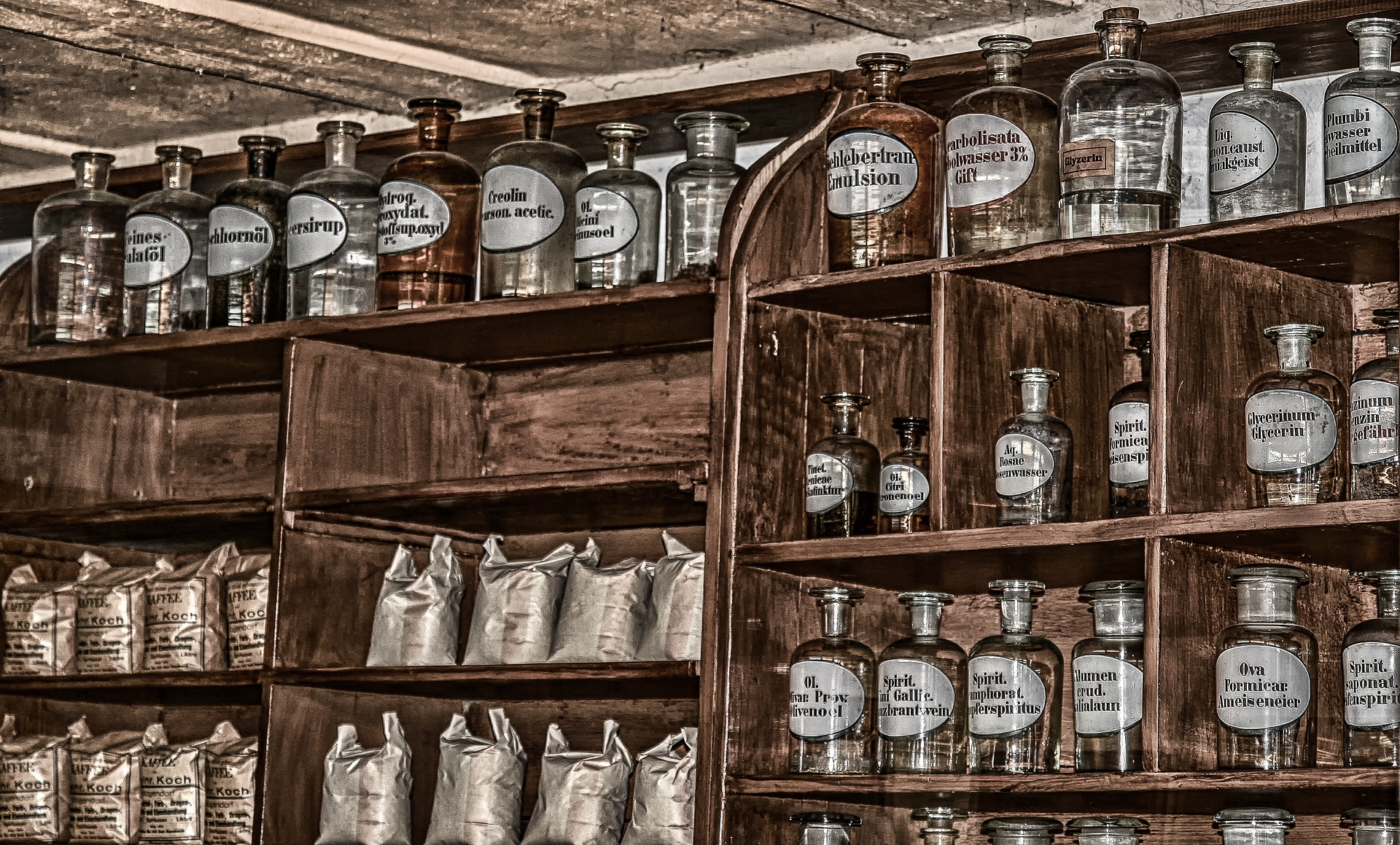 Kuvassa on vanhan apteekin puinen hyllykkö, jossa on kymmeniä lasipurkkeja ja pusseja..