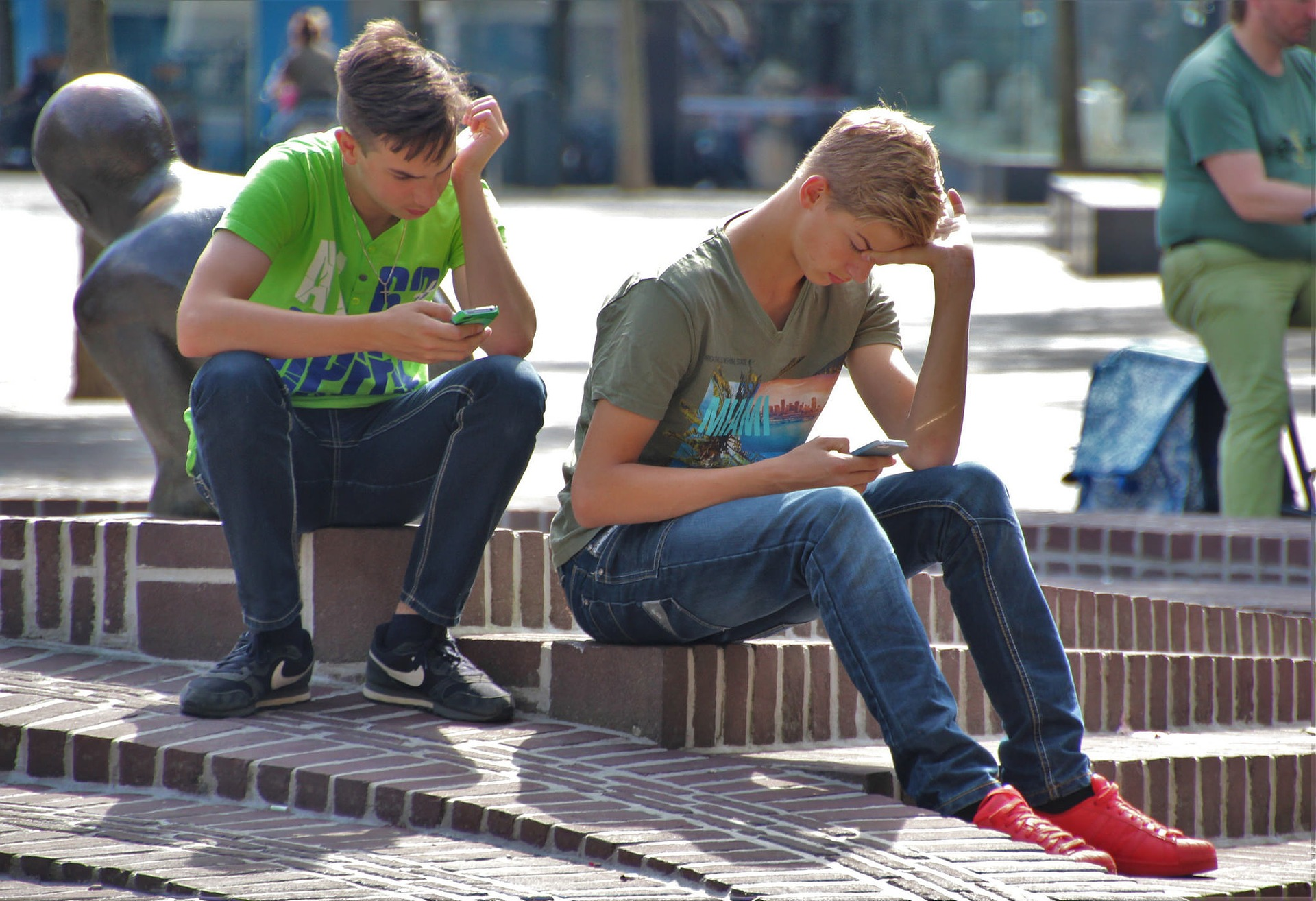 Kaksi nuorta miestä istuu ulkona ja ovat syventyneet puhelimiinsa, vieressä metallinen patsas.
