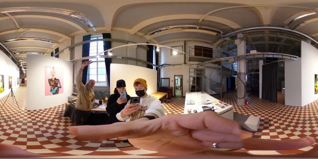 Vaakakuva, joka otettu 360-tekniikalla ja kuva on reunoista vähän pyöristynyt. Aiheena Galleri Huuto näyttelytilat ja kuvassa näkyy näyttelytilaa, etualalla käsi ja taustalla kaksi miestä.