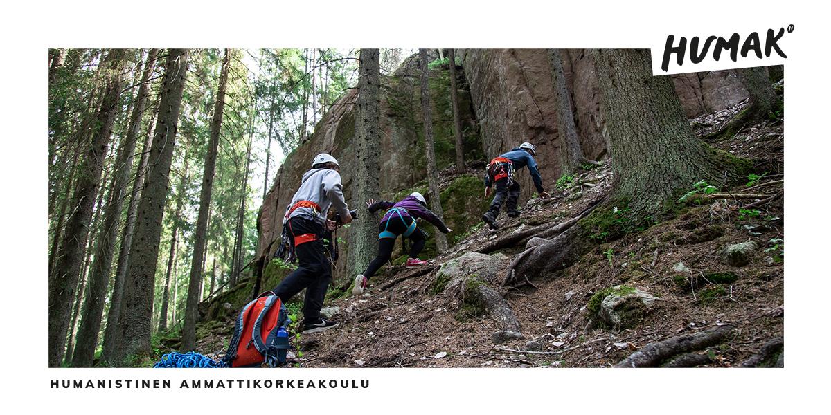 Seikkailukasvatus opiskelijat kiipeävät kallion rinnettä kiipeilyvarusteissa.