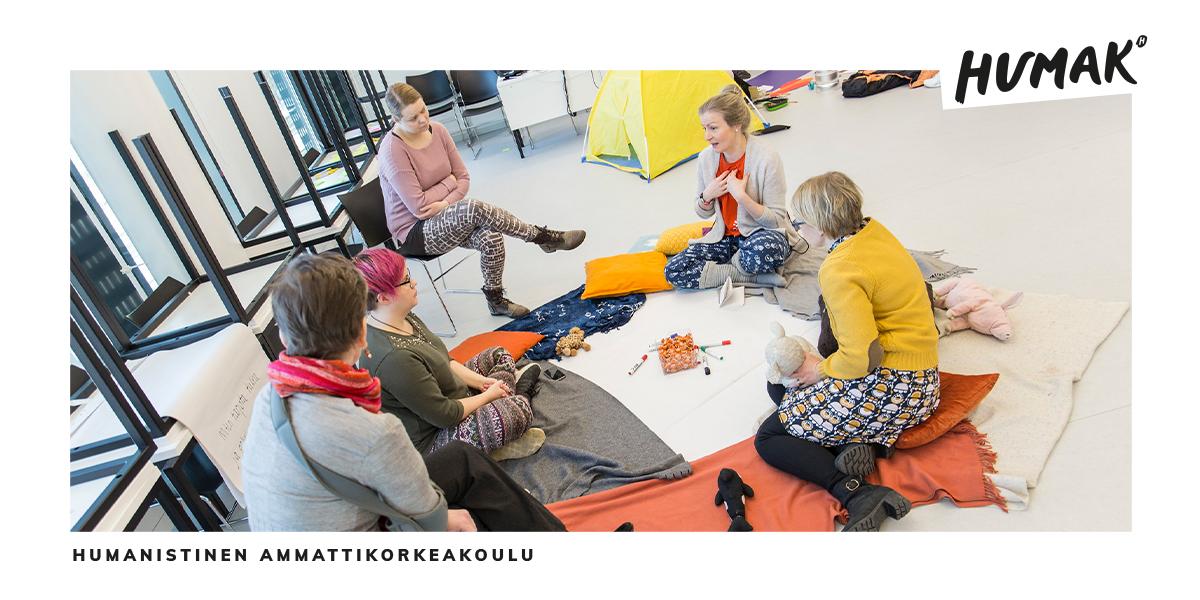 Viisi henkilöä istuu lattialla ja keskustelee.