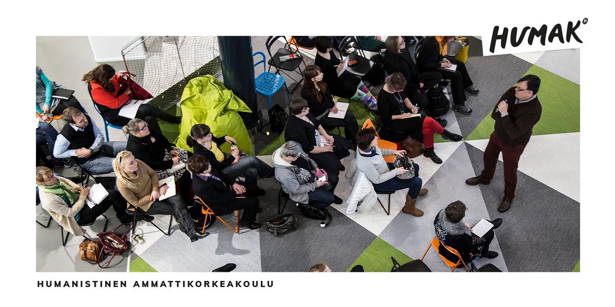 Ihmisiä istumassa penkeillä ja kuuntelemassa puhujaa.