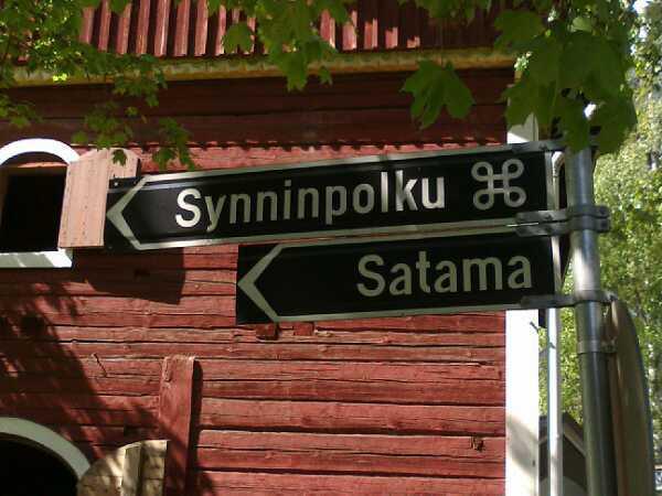 Etualalla tienviitat Synninpolku ja Satama, taustalla Korpilahden kotiseutumuseon punainen hirsiseinä kevätauringossa.