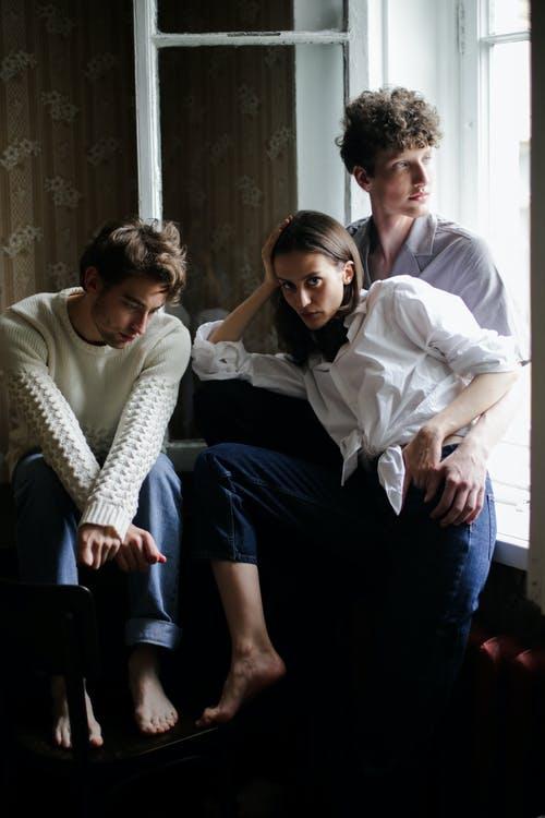 Kolme valkeisiin paitoihin ja sinisiin farkkuihin pukeutunutta, paljasjalkaista, nuorehka aikuista, kaksi miestä ja nainen istuvat avoimen ikkunan edeessä ryhmänä ja katsovat kaikki eri suuntiin.