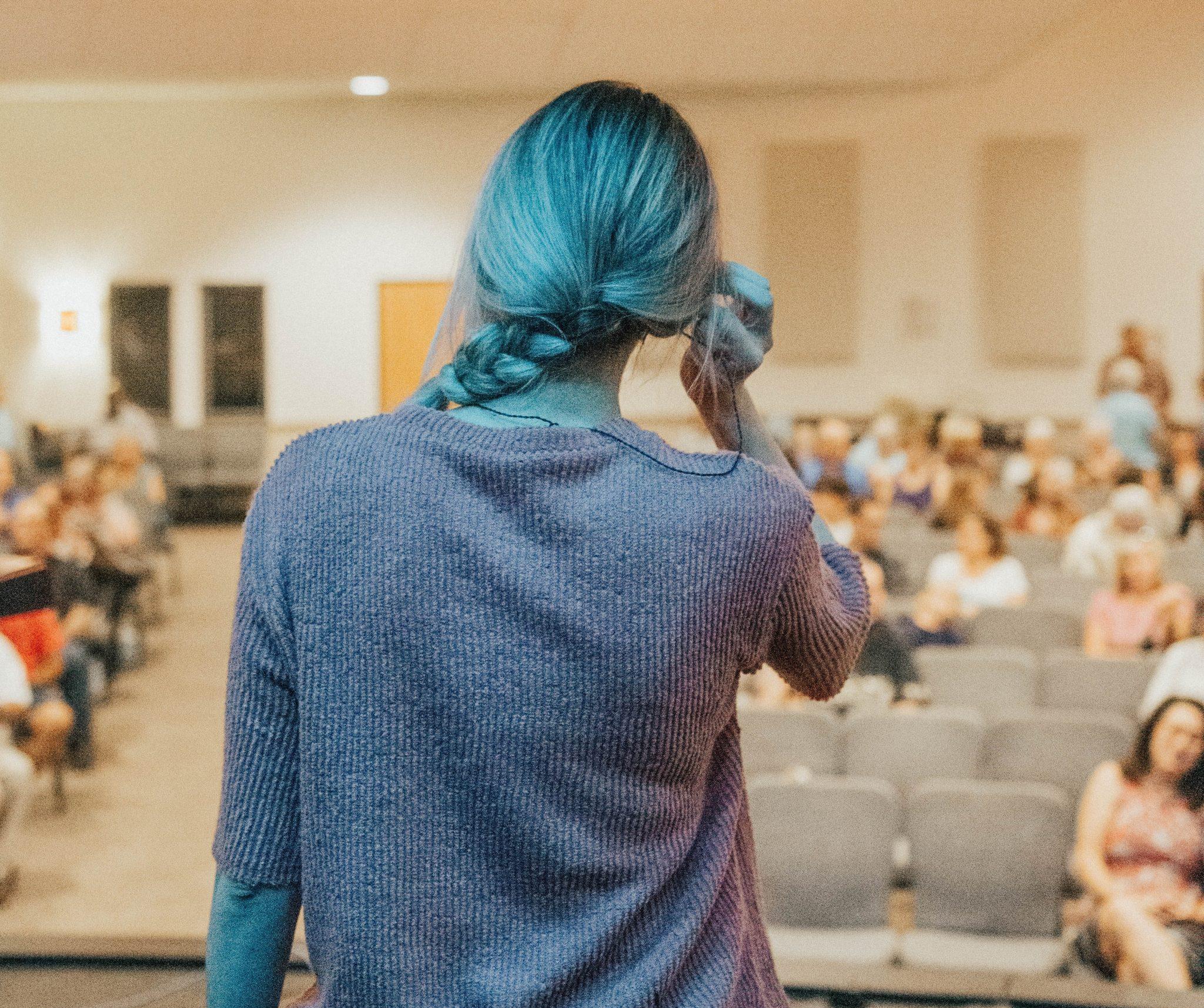 Nainen seisoo lavalla, selin kameraa kohti ja katsoo kohti yleisöä.