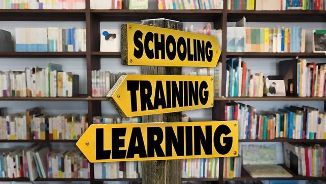 Kolme tienviittaa osoittaa eri suuntiin. Schooling oikealle; Training eteen vasemmalle ja Learning vasemmalle. Taustalla on kirjahylly.