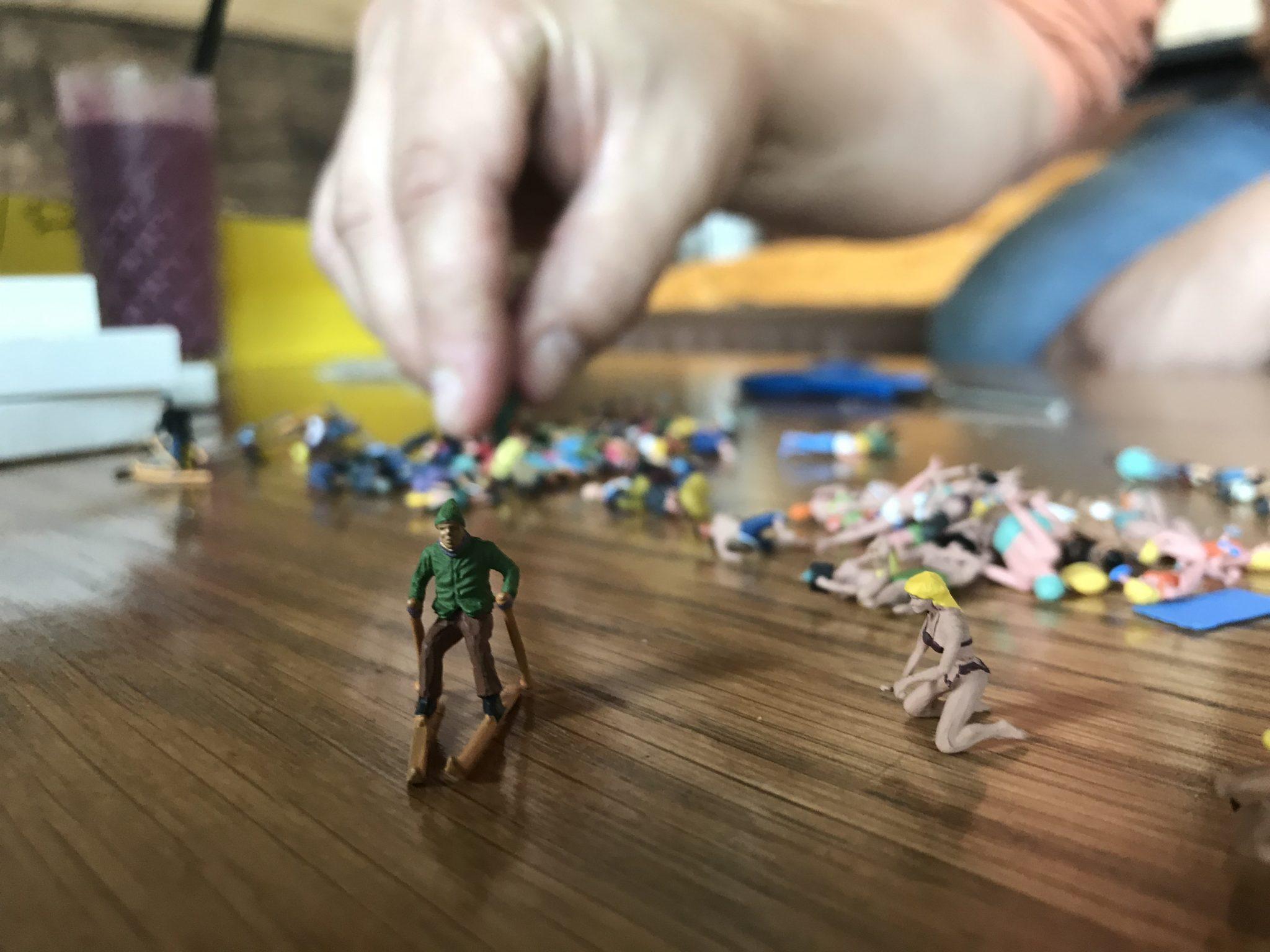 Pöydällä on kasa pieniä leikkifiguureja, jotka esittävät ihmisiä. Aikuisen ihmisen käsi kurottuu poimimaan yhtä niistä.