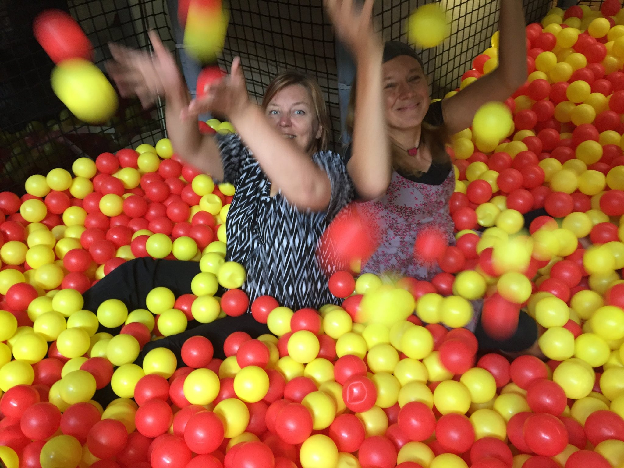 Kaksi aikuista ihmistä istuu pallomeressä, jossa on keltaisia ja punaisia palloja, ja heittää palloja ilmaan.