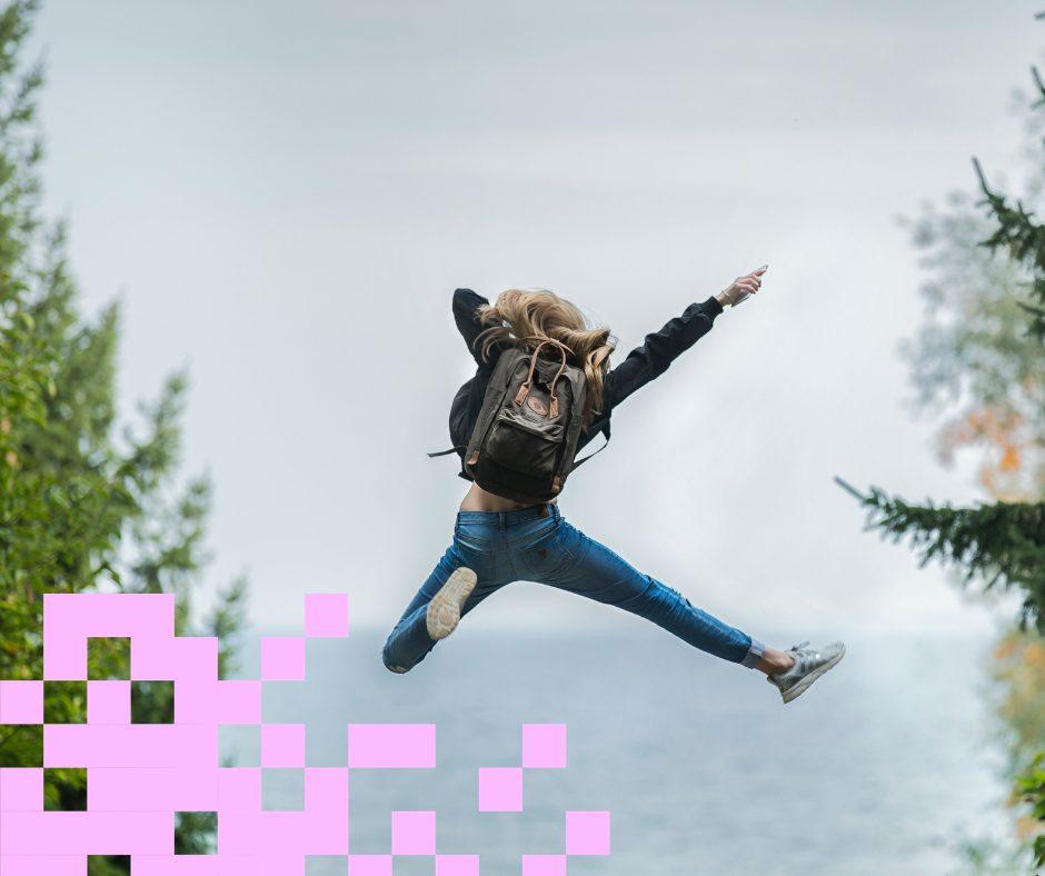 Tyttö hyppää korkealle, taustalla taivas.