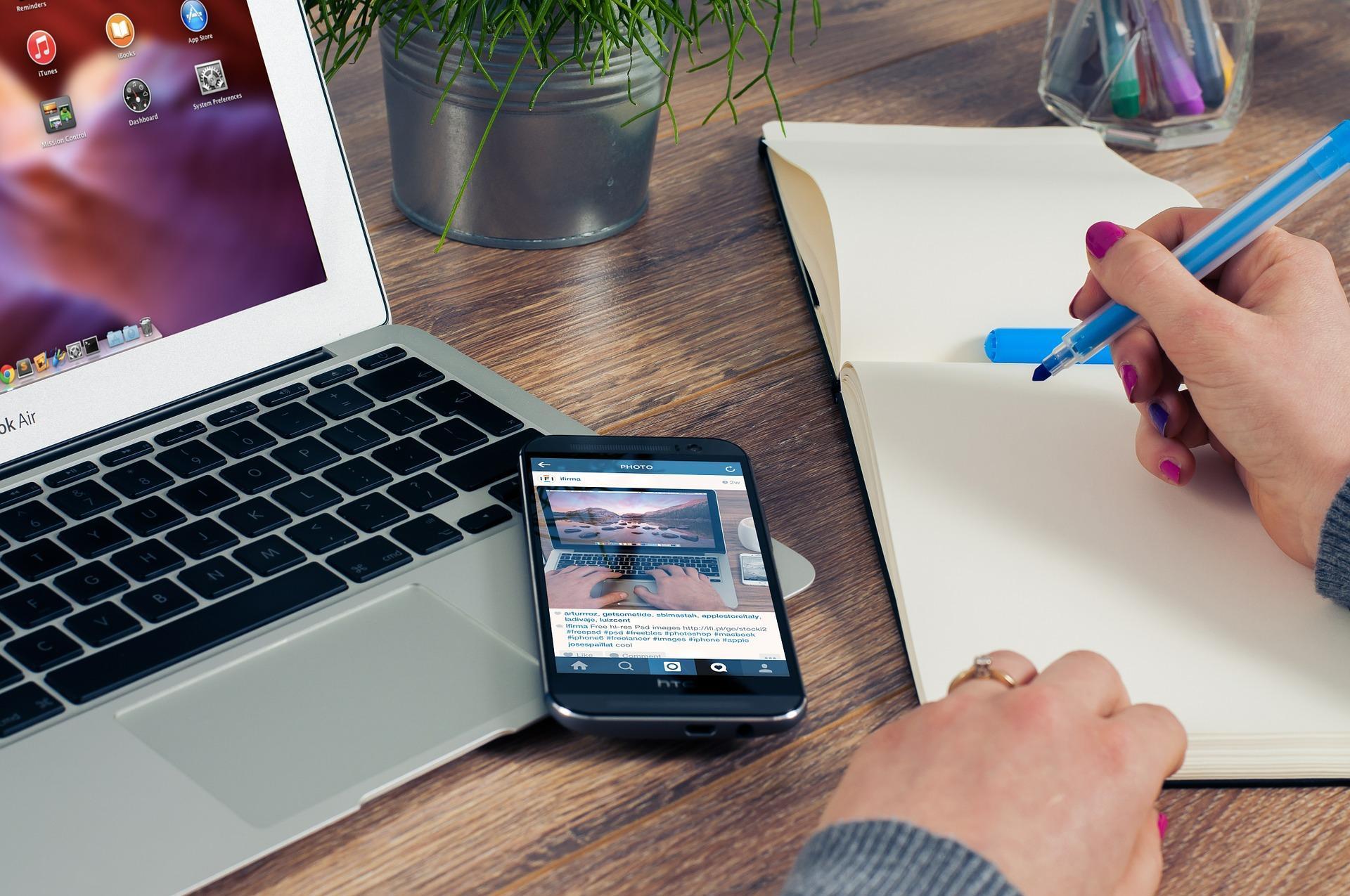 Puisella pöydällä kannettava tietokone, kännykkä, muistiopaperi ja kynäteline. Naisen kädet tussi valmiina kirjaamaan asioita.