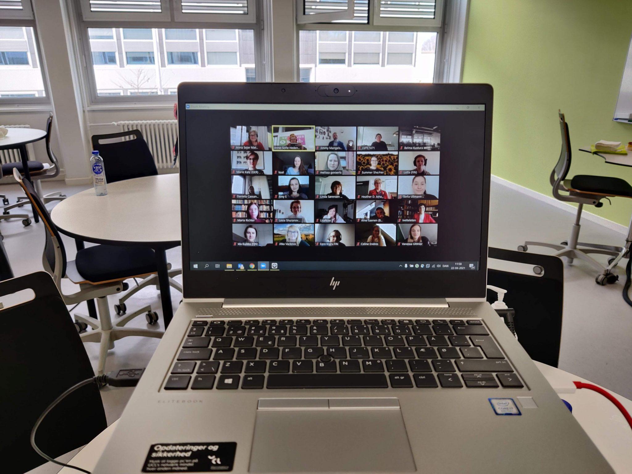 Kannettava tietokone jonka näytöllä Zoom-kokous jossa kymmeniä osallistujia.