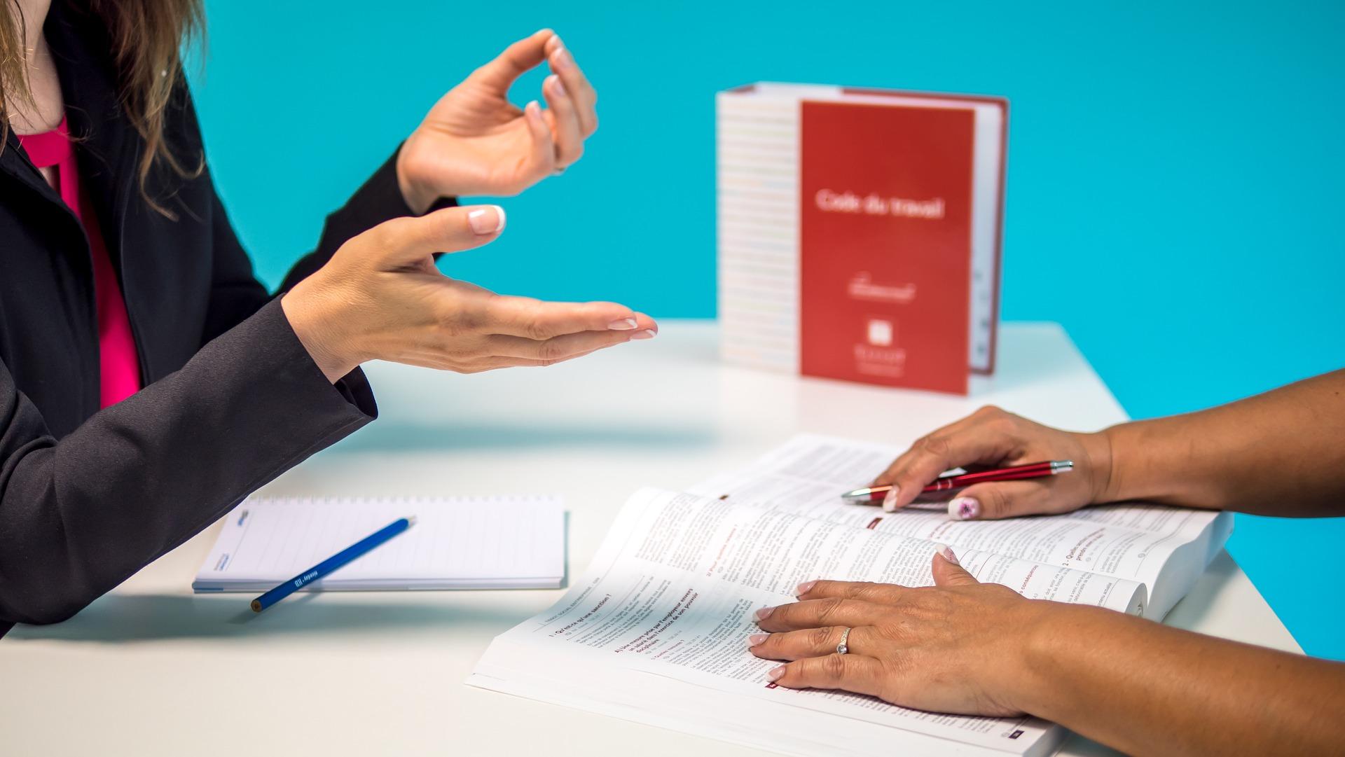 Henkilö istuu pöydän vastakkaisella puolella ja ohjaa käsillä elehtien muistiinpanoja kirjaan tekevää henkilöä.