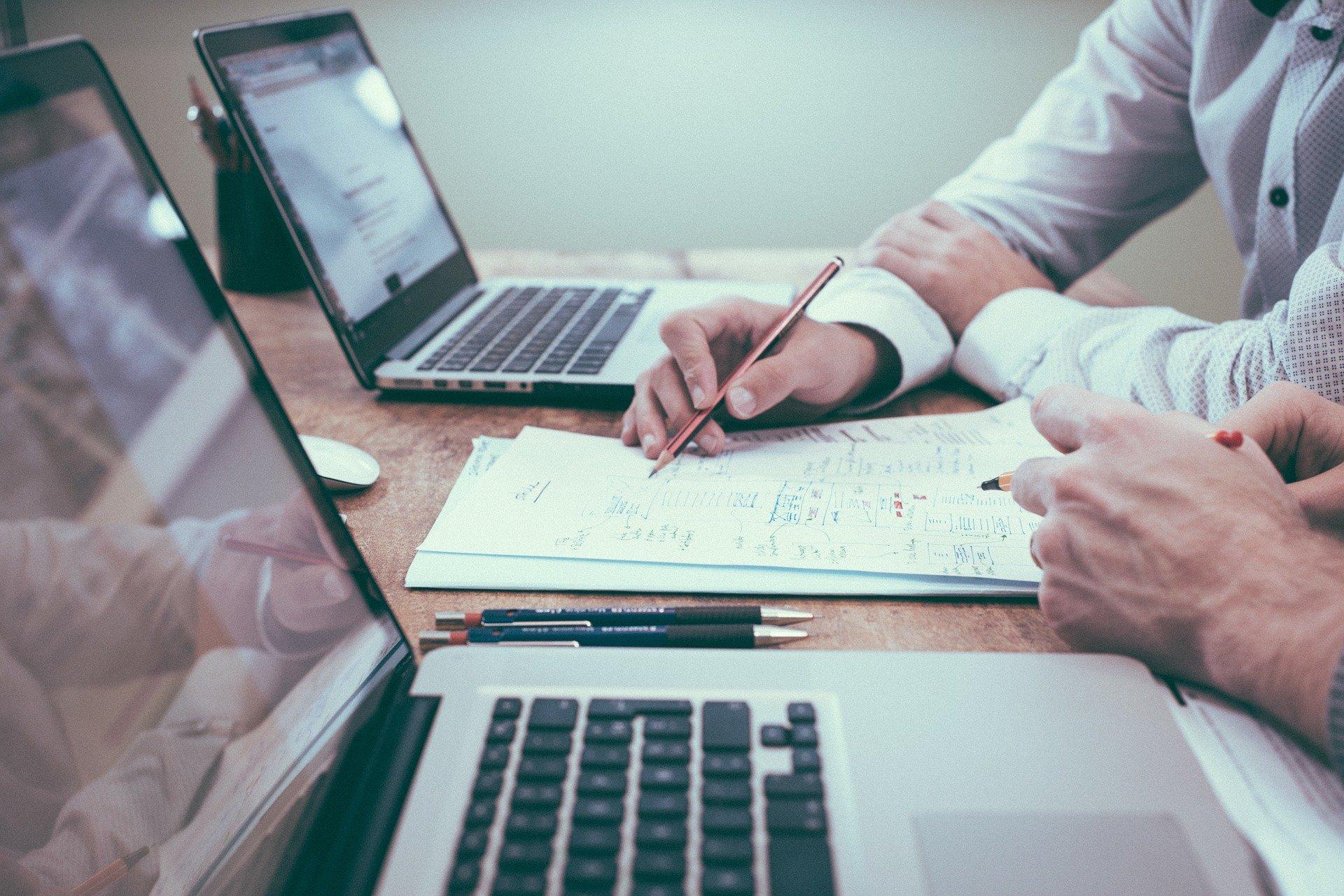 Kuvassa on kaksi henkilöä tietokoneiden äärellä tekemässä suunnittelutyötä paperille.