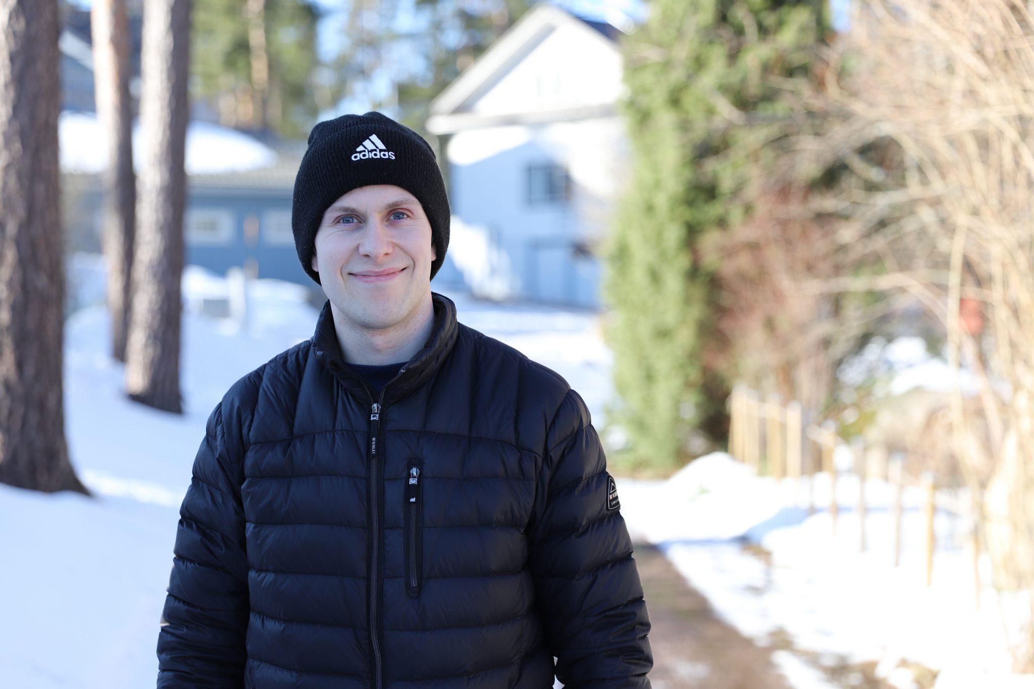 Mustaan pipoon ja takkiin pukeutunut mies hymyilee talvisessa maisemassa.